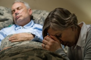 Uneasy senior woman praying for sick man
